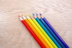 Различное покрашенное фото карандашей с космосом для текста 7 карандашей цветов радуги лежат на таблице Copyspace задняя школа к Стоковые Фото
