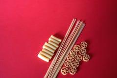 Различное смешивание сырцовых макаронных изделий на красной предпосылке Стоковая Фотография RF
