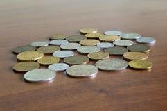 Различное собрание монеток на деревянном столе Стоковые Изображения