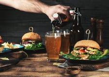 Различные бургеры с светлым пивом на деревянном столе Стоковые Фотографии RF