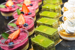 Различные виды сладостного десерта испекут с ягодами и зеленым te Стоковая Фотография