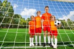 Различные дети высоты стоят в линии с футболом Стоковые Фото