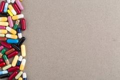 Различные красочные капсулы и пилюльки на коричневой бумаге ремесла Стоковое фото RF
