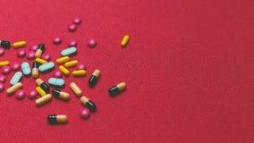 Различные красочные пилюльки, таблетки и капсулы на красной предпосылке Стоковые Изображения