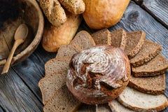 Различные куски на деревянном столе, комбинация хлеба печениь, хлеб рож с зернами, предпосылка еды Стоковые Изображения RF