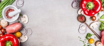 Различные овощи и специи варя ингридиенты с красной паприкой, минометом и пестиком и деревянной ложкой на каменной предпосылке ши Стоковые Фото