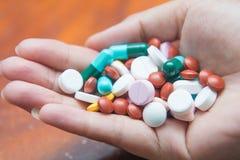 Различные пилюльки таблеток в руке Стоковая Фотография