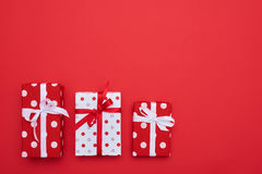 Различные подарочные коробки размера изолированные над красной предпосылкой Стоковые Фото
