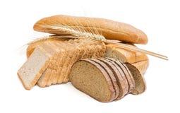 Различные продукты хлебопекарни и колоски пшеницы на светлом backgroun Стоковые Фото