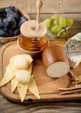Различные типы сыра, виноградины, мед, бутылка вина Стоковые Изображения RF
