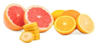 Различные цитрусы на белой предпосылке Отрежьте грейпфруты, зрелые апельсины, куски банана и кислые лимоны Освежая плодоовощи Стоковые Фото