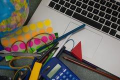 Различные школьные принадлежности и компьтер-книжка на доске Стоковое Фото