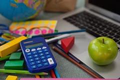 Различные школьные принадлежности, яблоко и компьтер-книжка на доске Стоковые Изображения