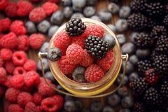 Различные ягоды в корзине на деревянном столе Стоковые Изображения RF