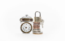 Различный стог монеток денег с padlock и ключи на верхней части около старых винтажных классических часов изолированных на белизн Стоковые Фото