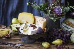 Различный сыр, свежие фрукты и цветки сада на старой древесине Стоковые Изображения