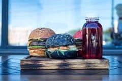 3 различных бургера на деревянной доске и соке Стоковая Фотография RF