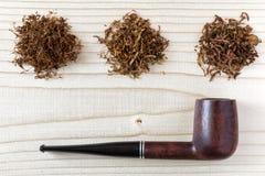 3 различных вида табака и трубы на деревянной предпосылке Стоковые Изображения