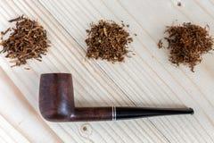 3 различных вида табака и трубы на деревянной предпосылке Стоковое Фото