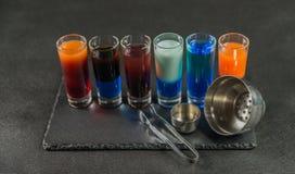 6 различных покрашенных пить съемки, выровнянных вверх на черном pla камня Стоковая Фотография RF