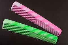 2 различных покрашенных щетки для волос на темной предпосылке Стоковые Изображения RF
