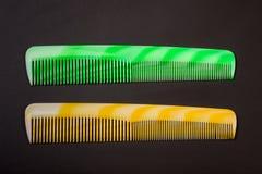2 различных покрашенных щетки для волос на темной предпосылке Стоковое Фото