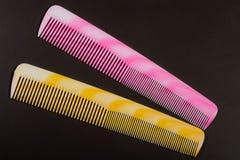 2 различных покрашенных щетки для волос на темной предпосылке Стоковые Изображения
