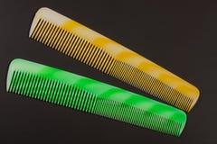 2 различных покрашенных щетки для волос на темной предпосылке Стоковые Фото
