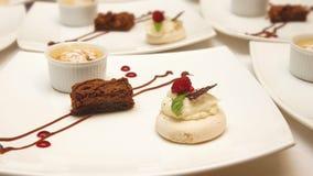 3 различных украшенных десерта служили в белых керамических квадратных плитах Стоковое фото RF