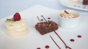 3 различных украшенных десерта служили в белых керамических квадратных плитах Стоковое Изображение
