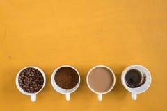 4 различных чашки на желтой предпосылке Стоковая Фотография