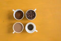 4 различных чашки на желтой предпосылке Стоковая Фотография RF
