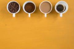 4 различных чашки на желтой предпосылке Стоковое Изображение RF