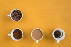4 различных чашки на желтой предпосылке Стоковые Изображения RF