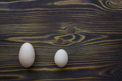 2 различных яичка размера на темной деревянной предпосылке говорят нам то Стоковая Фотография RF