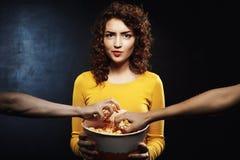 Раздражанная женщина держа ведро попкорна в руках смотря прямо Стоковые Фото