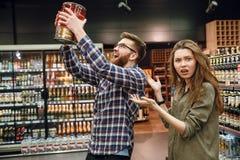 Раздражанная женщина показывая на человеке с бочонком пива стоковая фотография rf