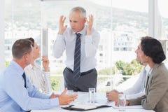 Раздражанный бизнесмен говоря к его команде Стоковая Фотография