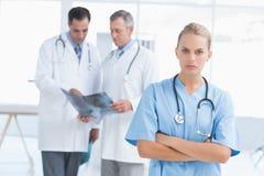 Раздражанный доктор смотря камеру пока ее коллеги работают Стоковое Изображение