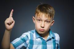 Раздражанный сердитый мальчик с угрожает пальца изолированного на серой предпосылке Стоковая Фотография