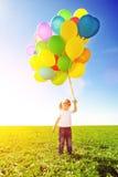 раздувает цветастое удерживание девушки немногая Ребенок играя на зеленом цвете Стоковые Фото