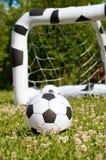 Раздувной шарик футбола ребенка на траве Стоковые Фото