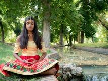 Раздумье красивой молодой индийской женщины практикуя в парке Стоковое Фото