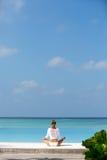 раздумье Фото женщины которая сидит в положении лотоса на побережье Мальдивах океана Стоковые Изображения RF