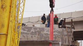 Район строительства моста, мужские работники идет, конкретный луч двинут краном сток-видео