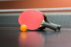 Ракетка настольного тенниса с шариком на черной таблице стоковые фото
