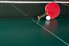 Ракетка пингпонга и шарик на зеленой таблице сеть пингпонга стоковые фото