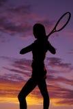 Ракетка тенниса женщины силуэта за заходом солнца стоковая фотография rf