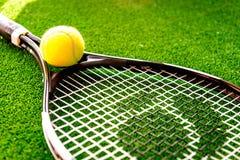 Ракетка тенниса на зеленом конце предпосылки вверх стоковое изображение rf