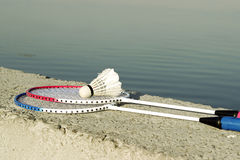 Ракетки бадминтона с shuttlecock на каменном стенде против Стоковые Фотографии RF